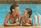 foto of swimming pool family  - Woman and girl in the swimming pool with cocktail - JPG