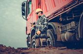 Caucasian Dump Truck Driver In His 30s And The Construction Site Full Of Dirt To Move. poster