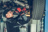 Caucasian Car Mechanic Adjusting Tension In Vehicle Suspension Element. Professional Automotive Serv poster