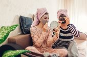 Mother And Her Adult Daughter Applying Facial Masks And Cucumbers On Eyes. Women Chilling And Having poster