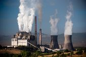Steaming smoke stack and cooling tower with pollution in Megalopolis, Greece