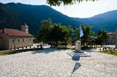 church and stone square with greek flag in mountain village of Koryshades, Greece