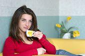 una chica guapa toma un descanso tomando un café en el sofá amarillo