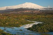 a seasonal river flows under the massive snowcovered Etna volcano at the evening