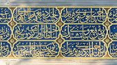 front view arabian calligraphy golden on blue background in Sultanahmet, Istanbul