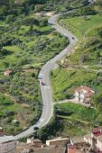 aerial view of cars are going through a winding rural road