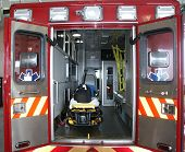 Paramedic's truck with open back doors, where stretcher and medical equipment is visible. All tradem