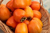 Persimmon Fruits And Persimmon Leaves In A Wicker Basket. poster