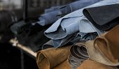 Different Pieces Of Leather In A Rolls. The Pieces Of The Colored Leathers. Rolls Of Blue And Black  poster
