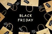 Craft Paper Shopping Bag On Black Isolated Background With Wooden Text black Friday And Sale Label poster