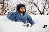 Child playing in the snow with snow on his face
