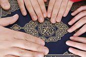 Hands unity on holy Koran