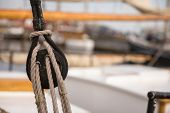 Pulley For Sails And Ropes Made From Wood On An Old Sail Boat, With Sail And Other Boats Out Of Focu poster