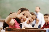 Happy children smiling and laughing in the classroom, showing thumb up, successful pupils and teache