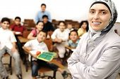 arabic Muslim kids in the school, classroom with a female smiling teacher