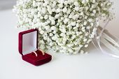 Wedding Rings In A Red Velvet Box And A Bridal Bouquet Over A White Table poster