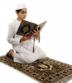 Arabic Muslim kid showing Islamic prayer and reading Holy Islamic book Koran