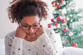 Worried Black Young Woman Sitting In The Living Room At Home During Christmas Holiday poster