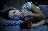 Young Sleepy Female Using Mobile Phone, Yawning Late At Night, Lying In Bed. Smartphone Addiction Co poster