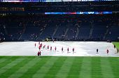 ATLANTA, GEORGIA - JUNE 16: Stadium workers place plastic on the field as rain caused delays during