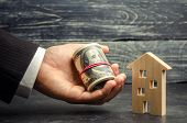 Wooden House And Money In Hand. A Loan Secured By Real Estate. Home Renovation And Repair. Warm Loan poster