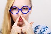 Nerdy Woman Holding Nose Smelling Bad Scent poster