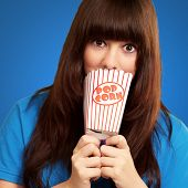 girl looking through empty popcorn packet isolated on blue background