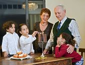 stock photo of dreidel  - grandparents and grandchildren lightening Hanukkah Menorah together - JPG