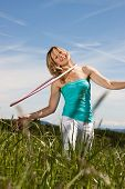 foto of hulahoop  - Young woman standing on a lawn and trained with hula hoops - JPG