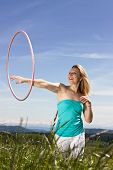 foto of hulahoop  - Blond woman standing on a lawn and plays with hula hoops - JPG
