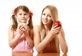 happy teeny girl with red apple and little girl with cake, isolated on white background
