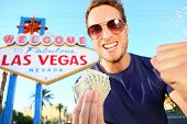 Las Vegas man winning money. Winning gambler standing excited in front of Welcome to Fabulous Las Vegas sign.