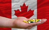 Holding Pills In Hand In Front Of Canada National Flag