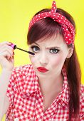 Funny portrait of girl applying mascara