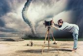 woman, taking photo by vintage camera and tornado (Photo compilation. Photo and hand-drawing elements combined. The grain and texture added.)