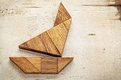 stock photo of tangram  - abstract picture of a sailing boat built from seven tangram wooden pieces over a rustic white painted barn wood - JPG