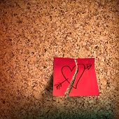 Red sticky note with heart sketched on cork board