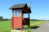 stock photo of bus-shelter  - Rural bus stop shelter made of wood and painted red by highway on a sunny day at summer - JPG
