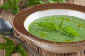 foto of nettle  - Nettle cream soup on wooden background - JPG