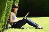 Mulher atraente e feliz em um parque com um Laptop