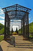 picture of pergola  - A metal pergola at the Randolph Street entrance to Maggie Daley Park in the Loop area of downtown Chicago is backlit against a bright blue sky - JPG