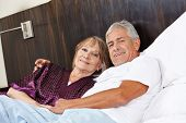 Senior couple in love cuddle in a hotel bed
