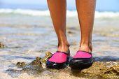 Sapatos de água / natação sapato em neoprene rosa em rochas na água na praia. Closeup detalhe dos pés