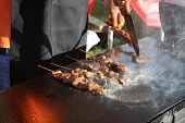 pic of barbie  - a picture of a chef cooking meat on a grill - JPG