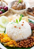 Nasi lemak traditional malaysia spicy rice dish, fresh cooked with hot steam. Served with belacan, ikan bilis, acar, peanuts and cucumber. Decoration setup, malaysian cuisine.
