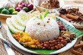 Nasi lemak traditional malaysian hot and spicy rice dish, fresh cooked with hot steam. Served with b