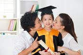 Kindergarten graduation. Asian family, grandparent and parent kissing grandchild on her kinder graduate day.