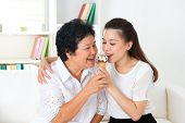 Sharing food. Happy Asian family sharing an ice cream at home. Beautiful senior mother and adult daughter eating dessert together.