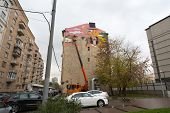 MOSCOW - OCT 10: The artist paints with colored inks the multi-storey building on the Astrakhan lane