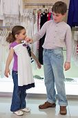 The boy helps sister to choose clothes in shop of childrens clothing